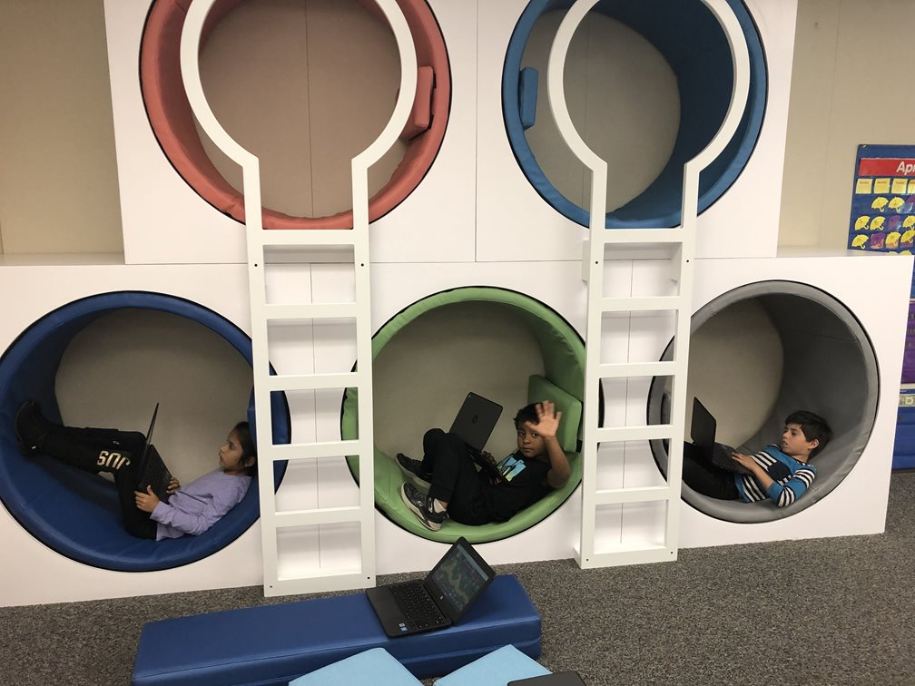 Students sitting in reading cubbies